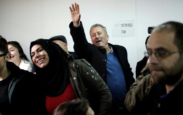 Photo du père d'Ahed Tamimi, Bassem (C), saluant sa fille de la main lors de l'ouverture du procès de la jeune palestinienne le 13 février 2018 devant le tribunal militaire d'Ofer, en Cisjordanie occupée