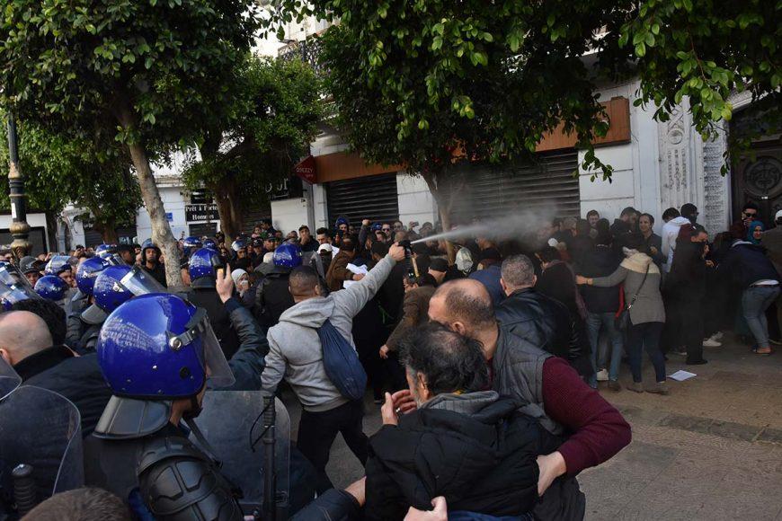 Un policier en civil asperge les manifestants avec le gaz lacrymogène. Ces derniers lui tournent le dos pour se protéger et se déplacent