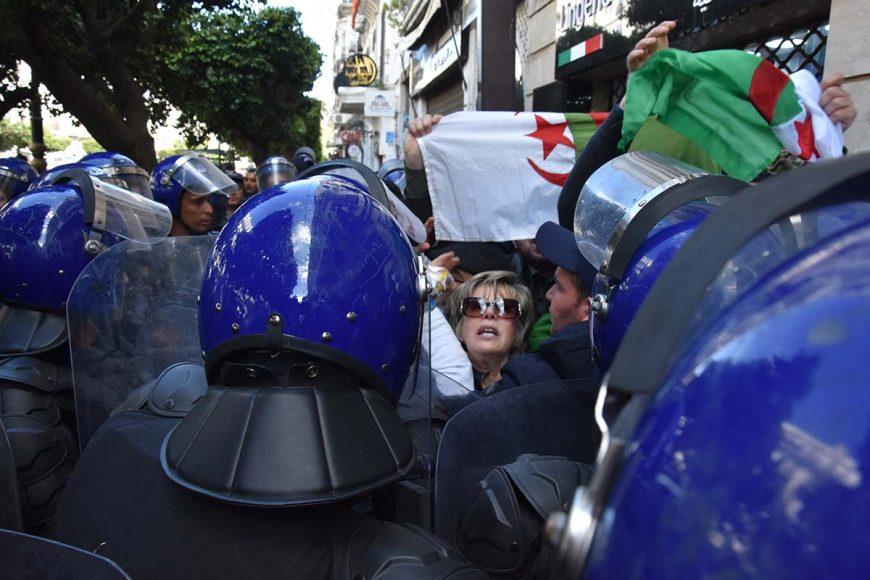 """L'ex coordinatrice du mouvement """"Mouwatana"""", Zoubida Assoul tente de forcer la barrière policière devant elle, et scandent des slogans contre le 5e mandat."""