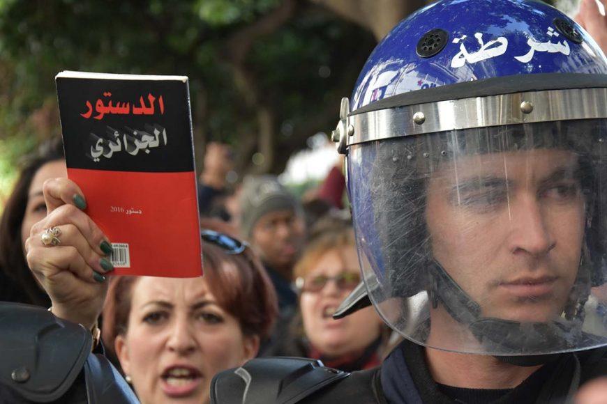 Cette femme qui a trouvé devant elle une barrière policière l'empochant de progresser, a préféré brandir la constitution algérienne au lieu d'une pancarte.