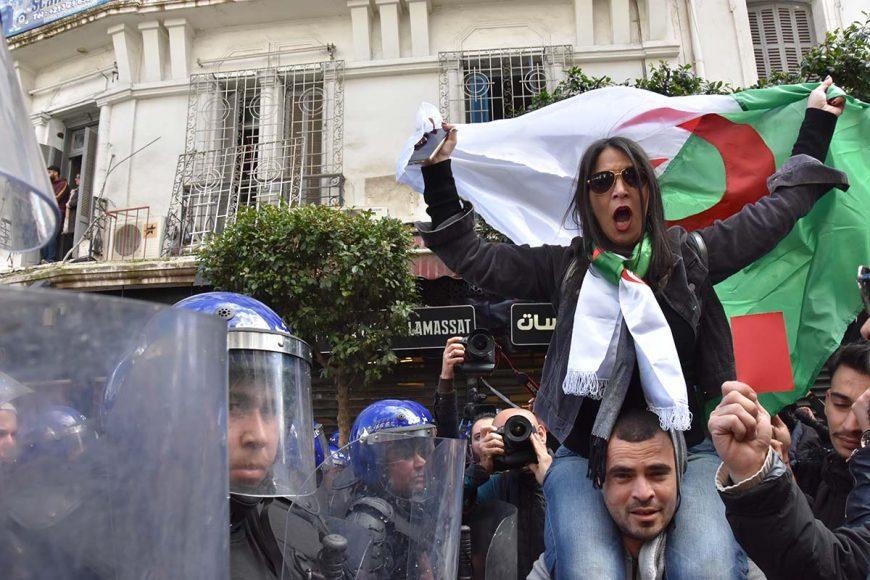 Cette femme qui brandit le drapeau algérien portée par un manifestant sur ses épaules, scande des slogans anti pouvoir face au cordon de CRS qui les empêchent de progresser pour rejoindre la place Maurice Audin.