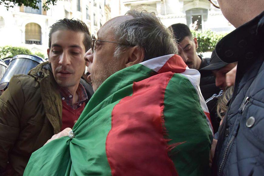 """Sofiane Djilali, Coordinateur de """"Mouwatana"""" couvert par un drapeau algérien au milieu des manifestants et des policiers."""