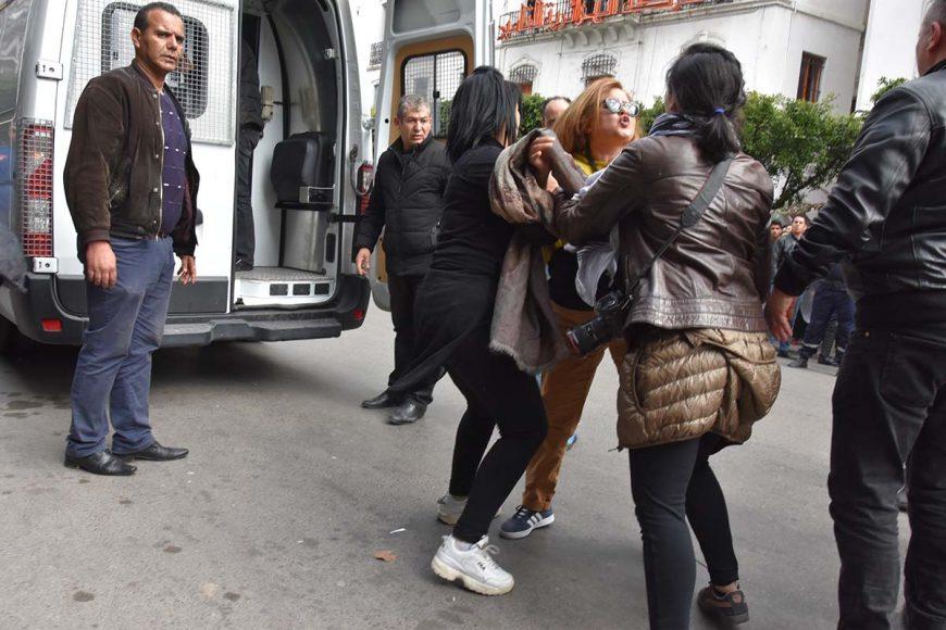 Interpellation d'une manifestante par deux policières en civile qui tentent de la mettre dans le fourgon cellulaire malgré sa résistance.