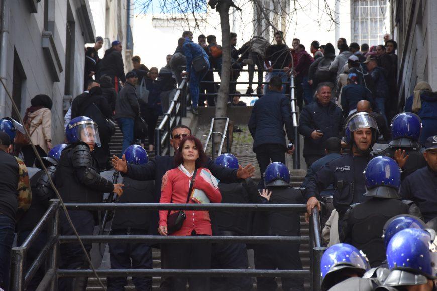 Un policier en civil protège une femme qui ne fait pas partie des manifestants, pour ne pas être bousculée par les CRS.