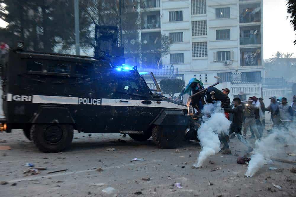 Des manifestants montent sur l'engin anti-émeutes et tentent de le casser.