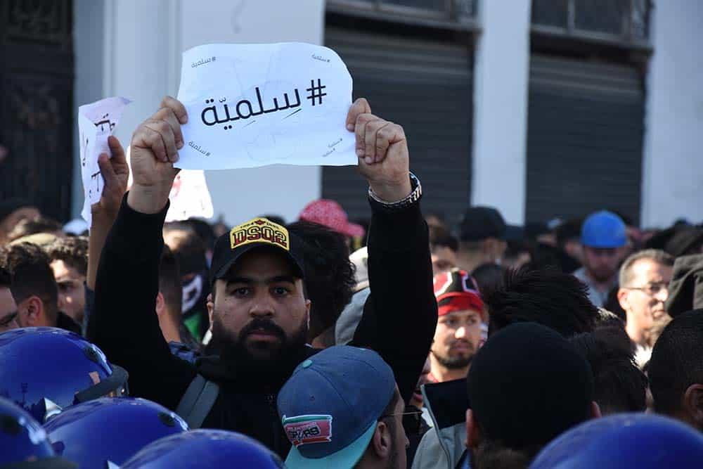 """Un manifestant qui oppose aux CRS une pancarte sur laquelle est marquée """"Silmiya (Pacifique"""""""