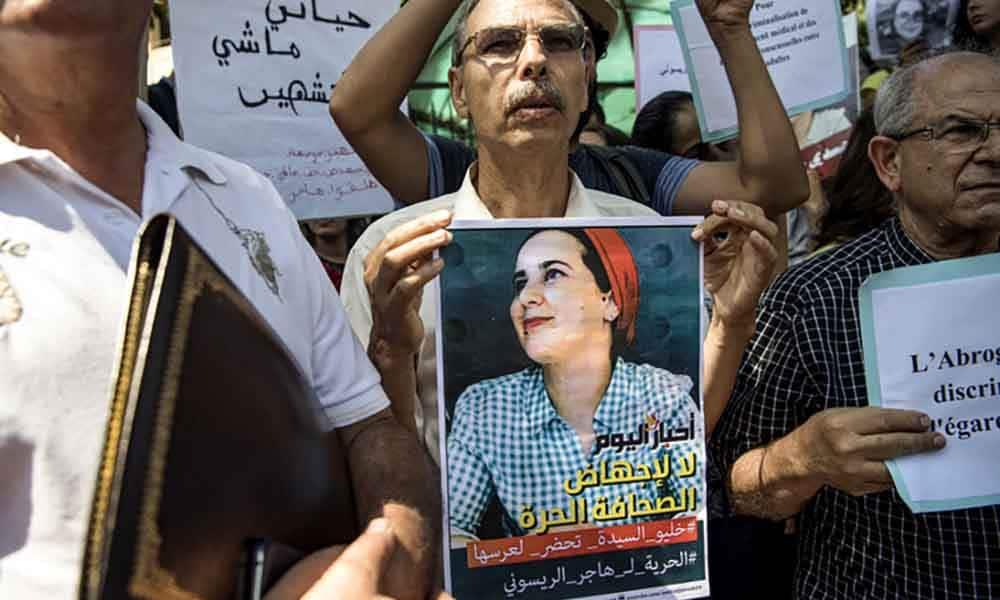 """Un manifestant marocain brandit le portrait de la journaliste Hajar Raissouni, jugée pour """"avortement illégal"""", le 9 septembre à Rabat"""