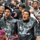 """Des manifestants sous des sachets en plastiques noirs sue lesquels est écrit """"État civil"""""""
