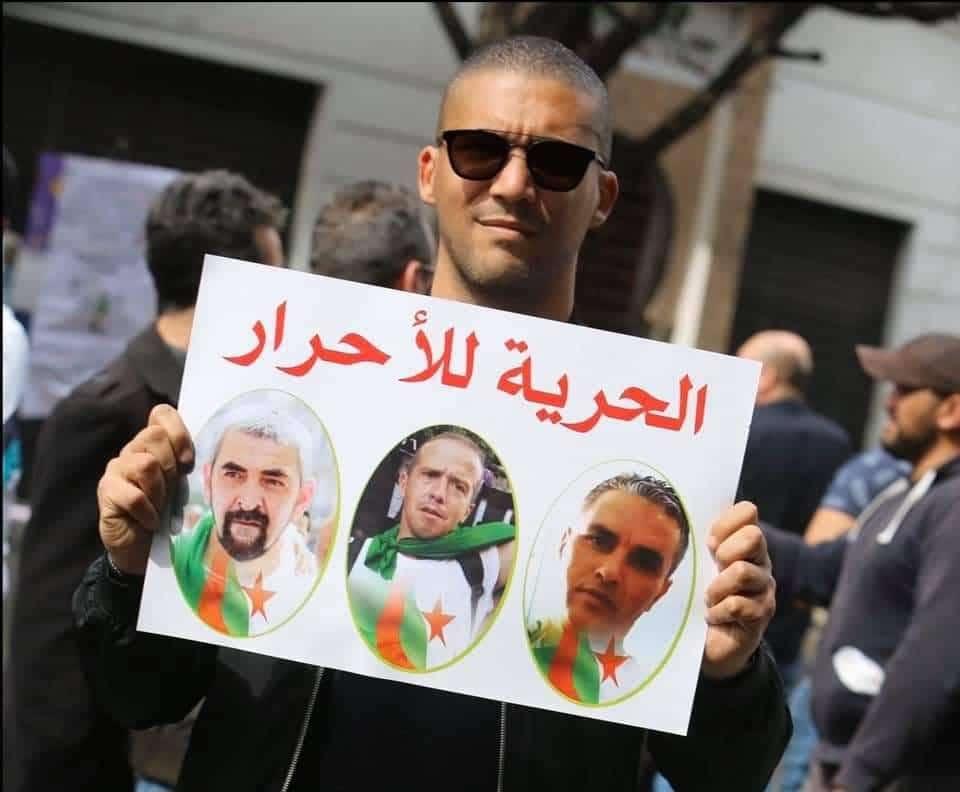 © DR | Khaled Drareni portant une pancarte en soutien à Samir Belarbi, Slimane Hamitouche et Toufik Hassani